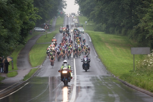 The peloton rides in one of the many rain showers during the Aviva Women's Tour 2016 - Stage 2. A 140.8 km road race from Atherstone to Stratford upon Avon, UK on June 16th 2016. ©Velofocus